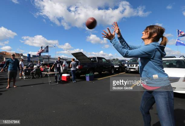 At right Rachel Teuber of South Boston plays catch with boyfriend Craig Legault of Duxbury in the parking lot at Patriot Place as fans tailgate...