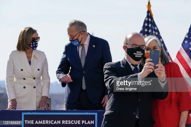 At right, Rep. Jim McGovern and Rep. Katherine Clark take a selfie together after Speaker of the House Nancy Pelosi and Senate Majority Leader Chuck...
