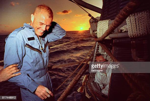At sea aboard destroyer NOA as the sun sets Lt Col John Glenn stands by as technician flown to the USS NOA from carrier Randolph prepares to remove...