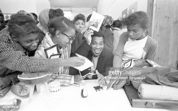 At Shepherd's Studio , photographer Billy 'Fundi' Abernathy signs cards for students and children during his 'Live Flicks of the Hip World'...