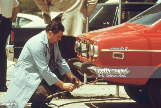 At Soldier's Field an automobile pollution test site an inspector wearing powder blue lab coat squats in the gravel road while fastening a tube to...
