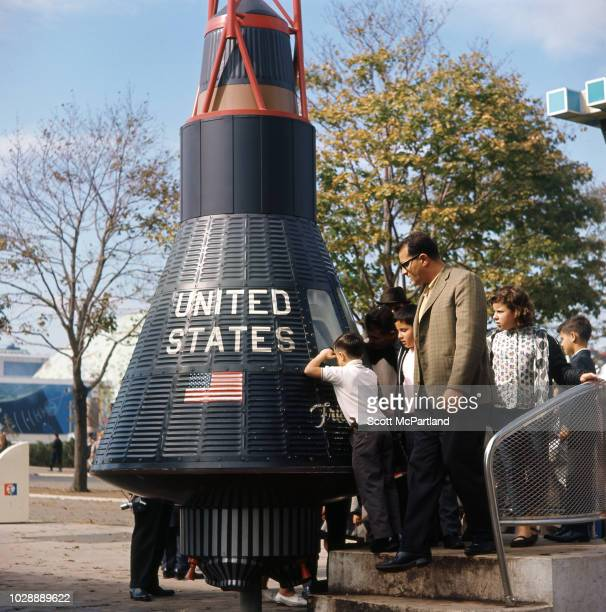 At Space Park exhibition a young boy at the head of a line looks through the porthole of NASA's Friendship 7 space capsule at the World's Fair in...