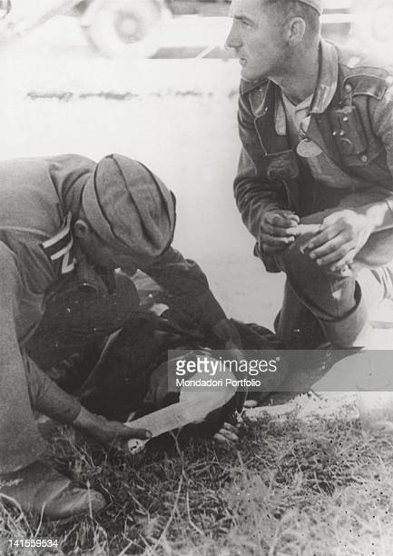 At Stalingrad present Volgograd a wounded Soviet prisoner receives medical aid from two German soldiers Stalingrad September 1942
