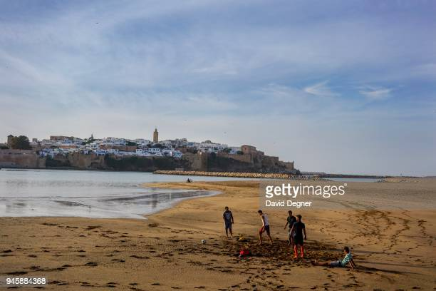 At sunest men play soccer on the beach at the mouth of the river between Rabat and Sale, Morocco. In the background the walls of the old city of...