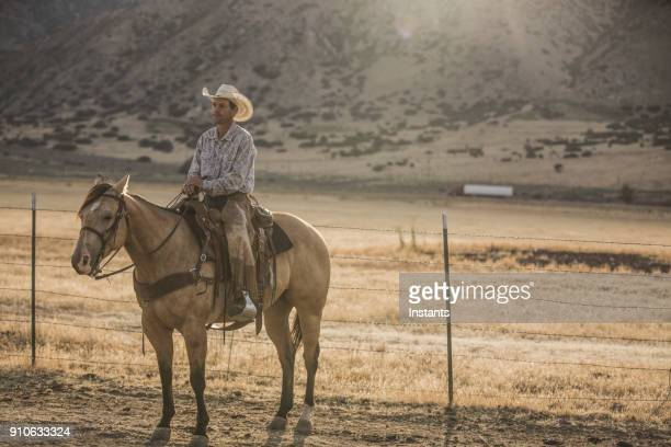 At sunrise, a cowboy on his horse is getting ready to start the day.