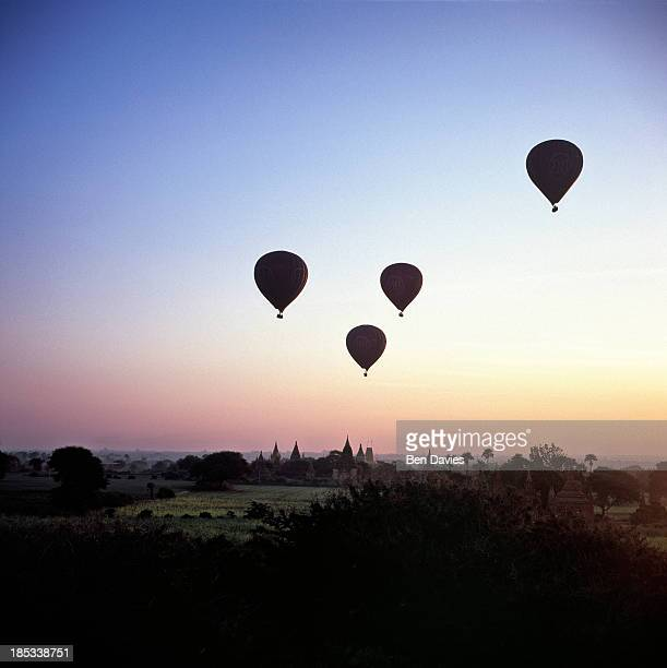 At sunrise four hot air balloons fly over the ancient temples of Bagan as viewed from the Shwesandaw Temple In all there are more than 2000 temples...