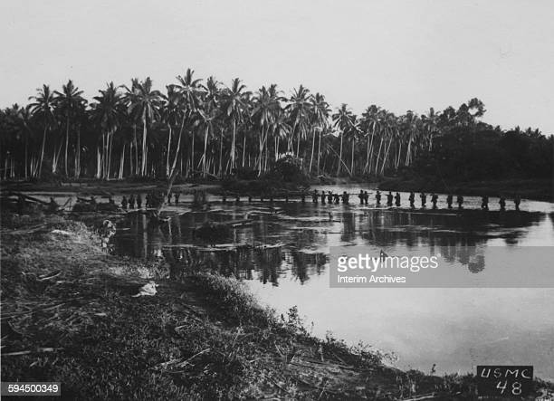 At sunset a United States Marine patrol starts out on a mission on Guadalcanal in the Solomon Islands 1942 They wade the shallow river in the first...