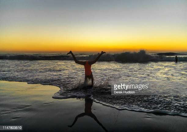 At sunset an unidentified girl stands on her head in the surf at Long Beach Kommetjie Kommetjie Western Cape South Africa May 1 2019