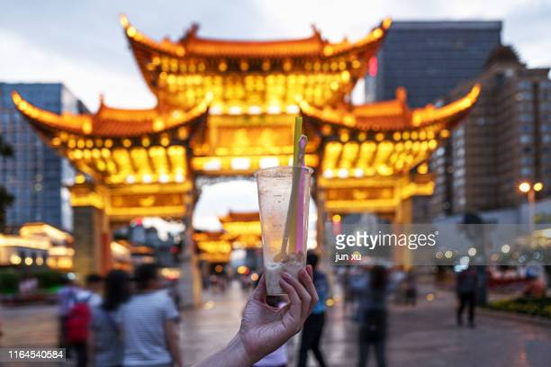 at sunset, the man holding lin under the golden horse and green chicken archway - kunming stock pictures, royalty-free photos & images