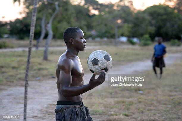 At sunset, young men play football, near the village of Kilwa Kivinje on the south coast of Tanzania.