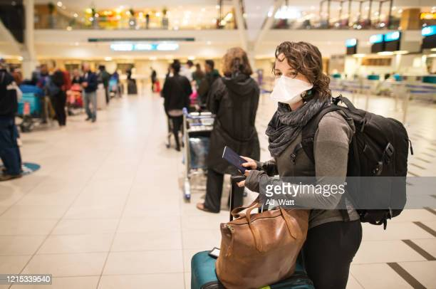 at the airport with a face mask - coronavirus airport stock pictures, royalty-free photos & images