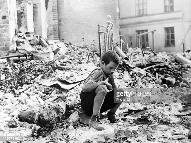 At the beginning of World War two a Polish boy sits grieving in the ruins of a street in Warsaw Poland September 1939