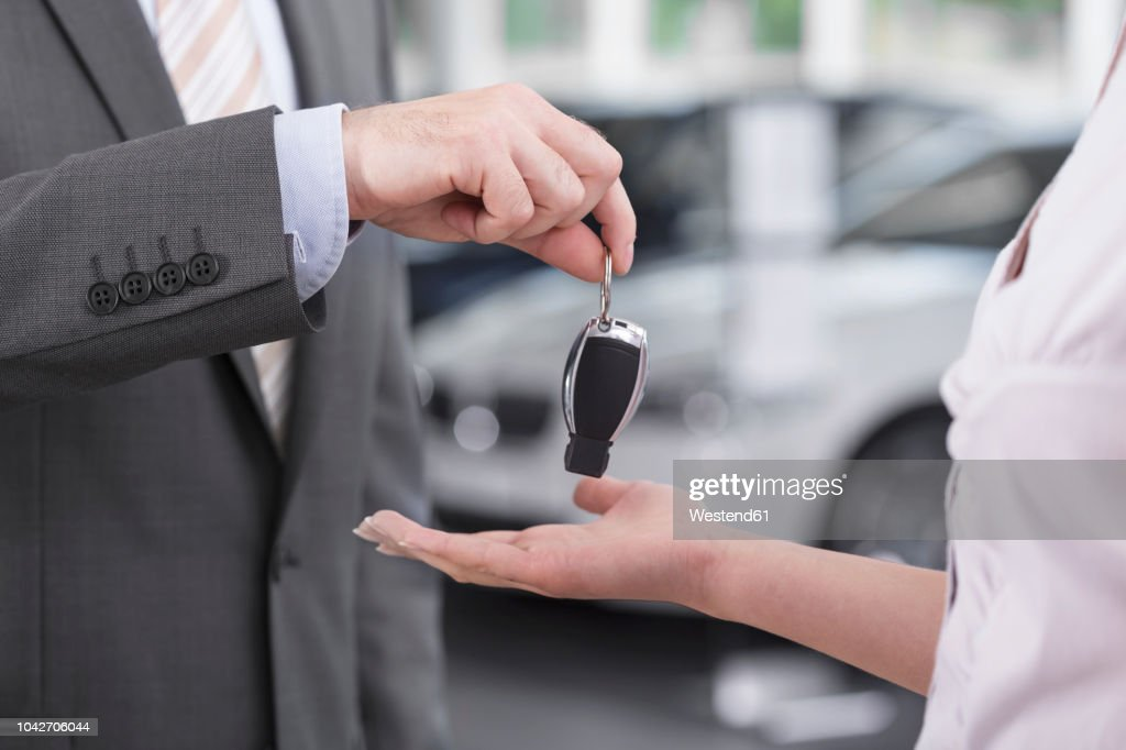 At the car dealer, Salesman handing over car key to client : Stock Photo