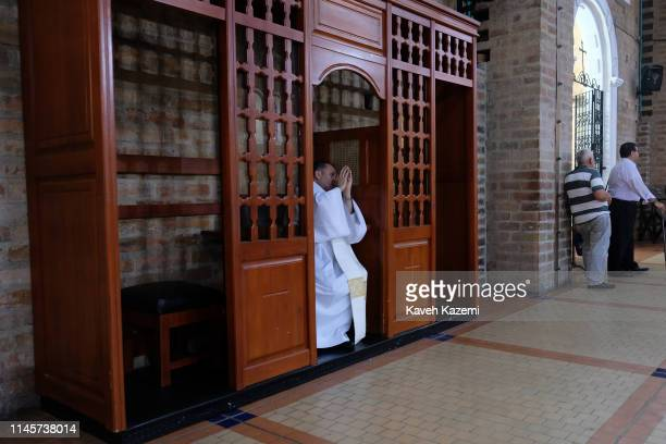 At the city Cathedral a priest in a confession booth raises his hands as a gesture of absolution to a person having had confessed to his sins in the...