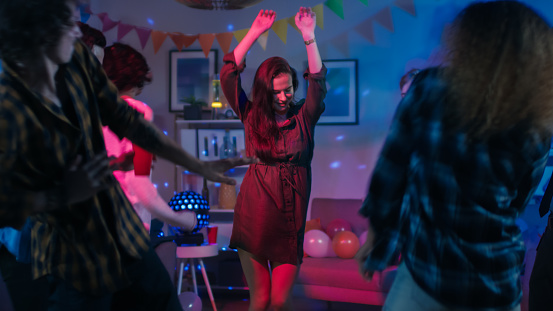 At the College House Party: Young Girl Dances in the Middle of a Circle of People. Diverse Group of Friends Have Fun, Dancing and Socializing. Disco Neon Strobe Lights Illuminating Room. 1160783618