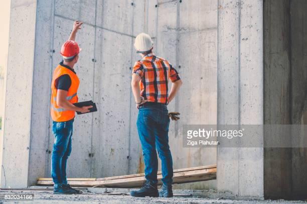 建設現場でエンジニアが結果を話し合う