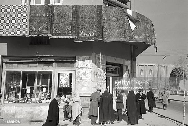 At the corner between two streets in Teheran, men wearing western clothes, and women veiled walk in front of a shop, in the day of the marriage...