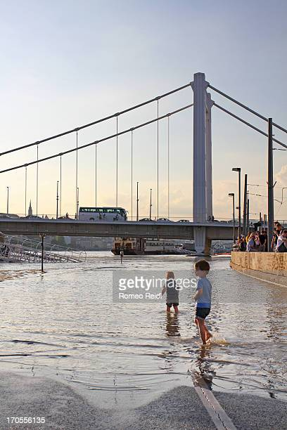 At the Danube flooding peak young children are playing in the water in the sunset just before the Elisabeth bridge.