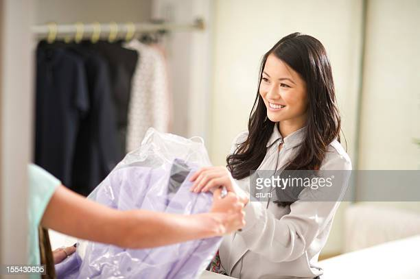 at the dry cleaners - dry cleaner stock pictures, royalty-free photos & images