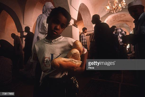At the end of a mourning ceremony a boy distributes bread April 2000 in Ghadames Libya