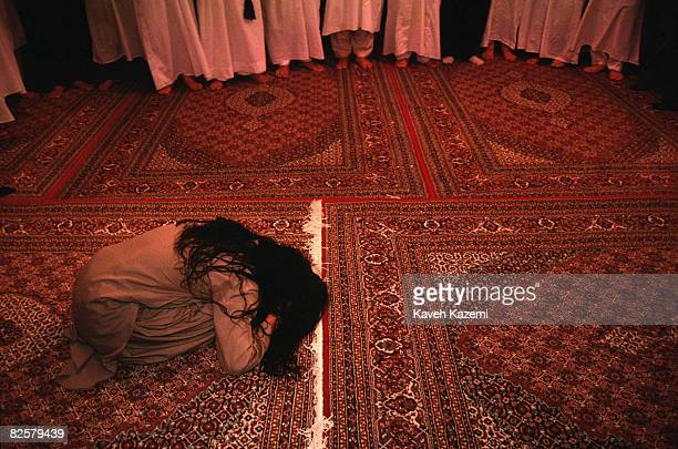 At the end of a remembrance ceremony in Sanandaj a Kasnazani dervish still in a trance kneels on the floor covered with Persian carpets surrounded by...