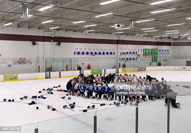 At the end of the game both teams meet on the ice to say a prayer The Regis Jesuit High School hockey team takes on Resurrection Christian High...