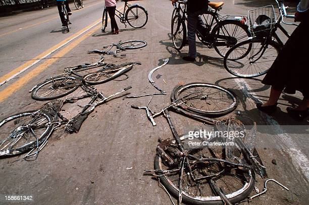 At the end of the prodemocracy movement in China cyclists stop to look at bicycles flattened by the Chinese army tanks that were used during the...