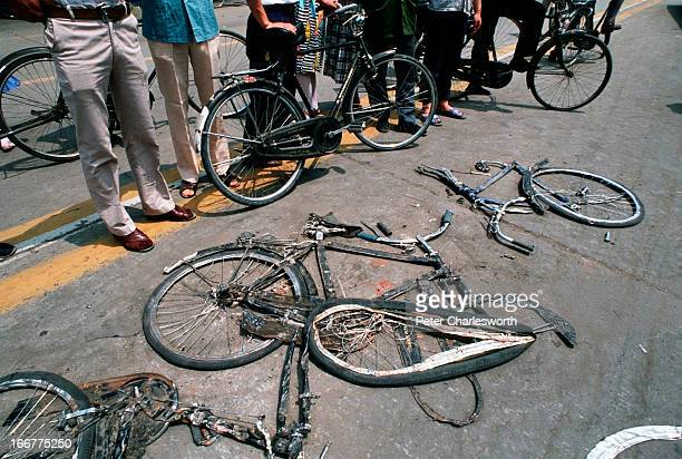 At the end of the pro-democracy movement in China, cyclists stop to look at bicycles flattened by the Chinese army tanks that were used during the...