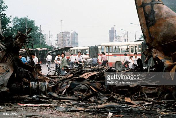 At the end of the prodemocracy movement in China onlookers examine destroyed buses once barricades that were run over by Chinese Army tanks during...