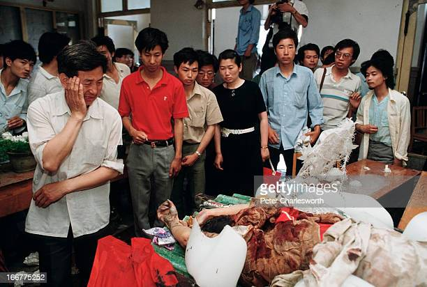 At the end of the prodemocracy movement in China onlookers examine the dead body of a protestor lying in a temporary morgue He was killed during the...