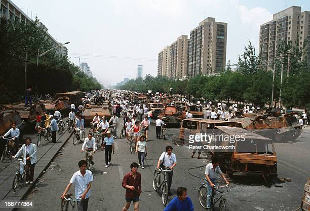 At the end of the pro-democracy movement in China, onlookers examine Chinese Army trucks and vehicles that were damaged or destroyed during the night...