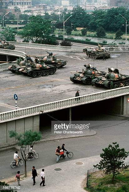 At the end of the pro-democracy movement in China, pedestrians and cyclists pass underneath a group of Chinese Army tanks. The tanks are blocking an...