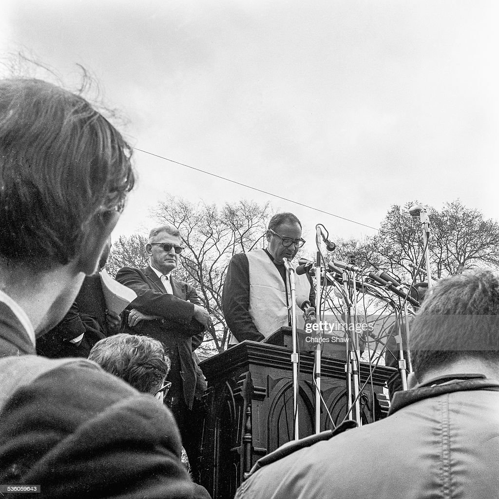 At the end of the Selma to Montgomery March, an unidentified Civil Rights activist speaks to the assembled marchers and spectators in front of the Alabama State Capitol, Montgomery, Alabama, March 25, 1965. The pulpit is from the Dexter Avenue Baptist Church, and it is the one from which Martin Luther King Jr preached his sermons when he was pastor there between 1954 to 1960. Several helicopters are visible above.