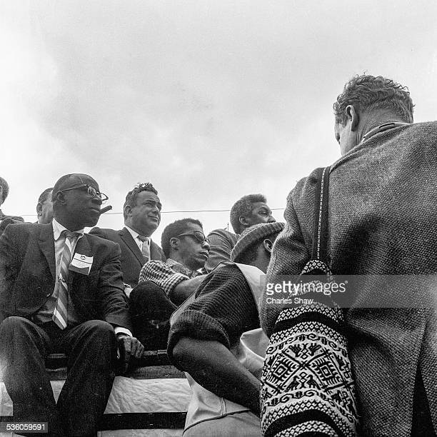 At the end of the Selma to Montgomery March writer and Civil Rights activist James Baldwin sits with others and listens to a speech on the podium in...