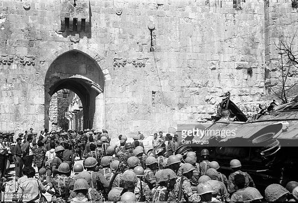At the end of the Six Day War Israeli soldiers file past a burnt vehicle as they enter the Lions' Gate Old City of Jerusalem Israel June 11 1967...
