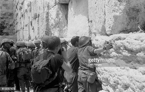 At the end of the Six Day War Israeli soldiers hug and kiss the stones of the Western Wall Old City of Jerusalem Israel June 11 1967 Israeli forces...