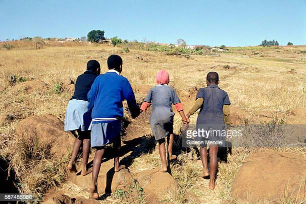 At the end of their school day these AIDS orphan girls walk to a community feeding centre in the Bhanganoma community in rural Swaziland Pumelele...