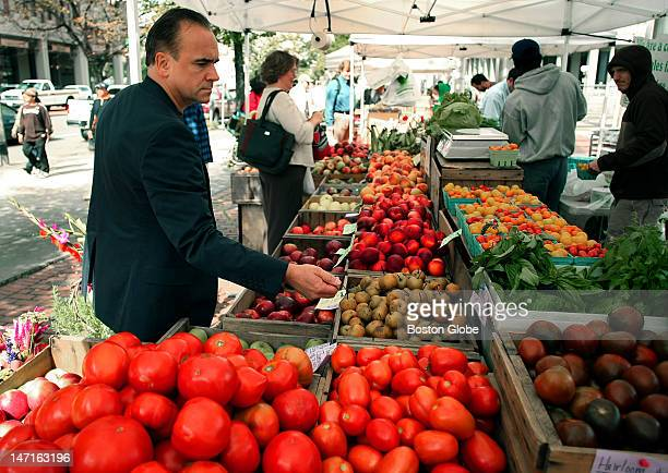 At the farmers market in Government Center in front of Boston City Hall New York chef Jean Georges Vongerichten checks out vegetables at a farm stand...