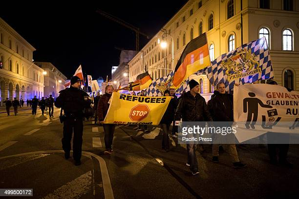 """At the front of a PEGIDA protest, a """"Refugees not welcome"""" flag is carried by demonstrators. As almost every Monday during the past year PEGIDA..."""