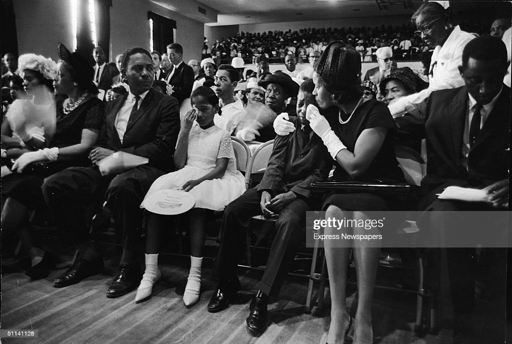 At the funeral for slain Civil Rights leader Medgar Evers, his wife, Myrlie Evers (second right), comforts their son, Darryl Kenyatta Evers, while daughter Reena Denise Evers (center, in white dress) wipes her own tears, Jackson, Mississippi, June 18, 1963.