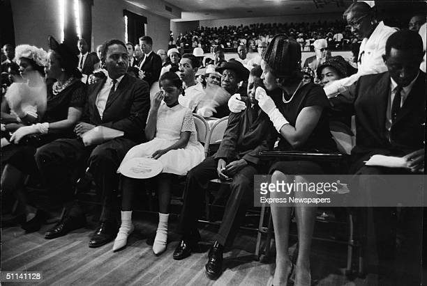 At the funeral for slain Civil Rights leader Medgar Evers his wife Myrlie Evers comforts their son Darryl Kenyatta Evers while daughter Reena Denise...