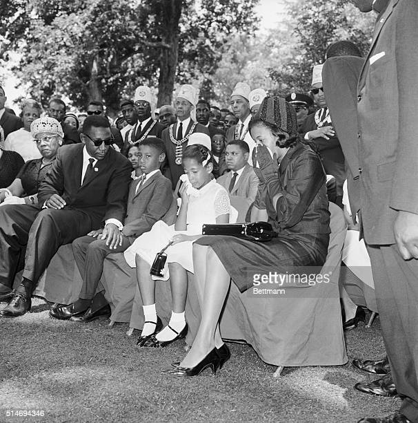 At the funeral of slain civil rights leader Medgar Evers Charles Evers brother of Medgar leans over to comfort Medgar's widow Myrlie and her children...