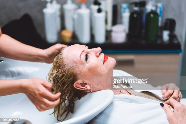 at the hairdresser washing her hair - residential care stock photos and pictures