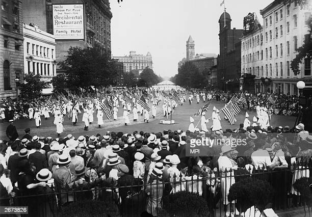 At the height of their power000 members of the American white supremacist movement the Ku Klux Klan parade down Pennsylvania Avenue in Washington DC