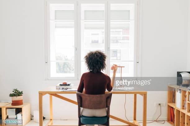 at the home office: african american woman sitting at her desk and working, a back view - back stock pictures, royalty-free photos & images
