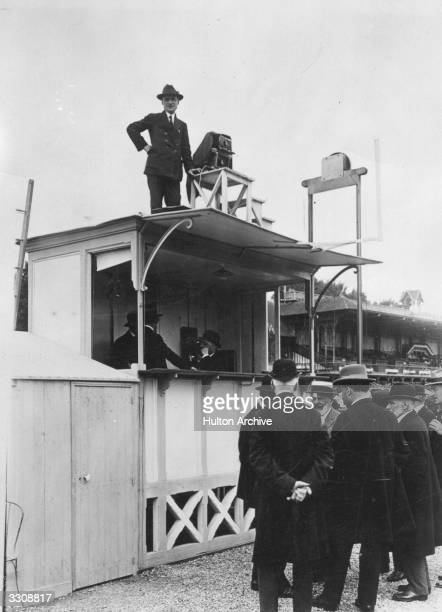 At the horse races new registering equipment is introduced to give a photo finish The photographer is seen over the judges box