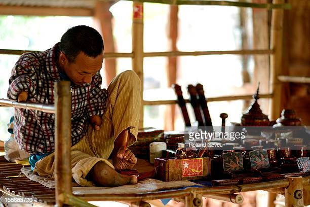 At the Indein covered walkway a Burmese handicapped man paint lacquer with his foot despite his disability he show a very good control of his...