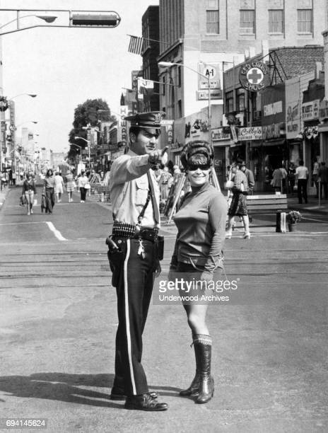 At the intersection of Main and Mercer streets a policeman gives directions to an unidentified young woman dressed in sunglasses a turtleneck...