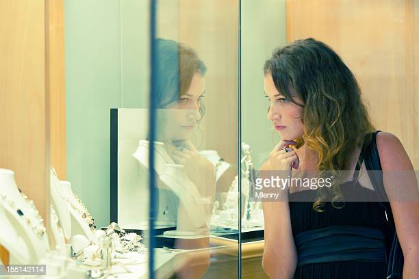 At the jeweller, woman looking inside shop window display