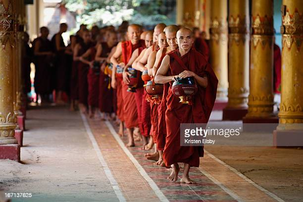At the Kha Khat Wain Kyaung monastery in Bago, hundreds of scarlet-clad buddhist monks line up silently with their traditional black lacquerware...
